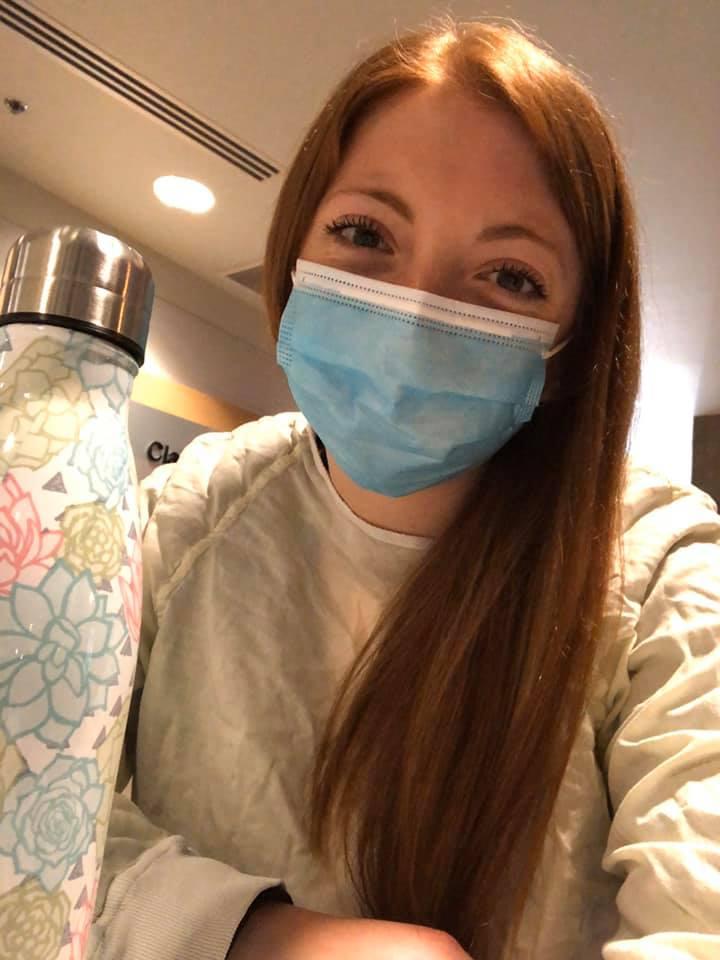 Jessika paradis souris derrière son masque en prenant une selfie au travail