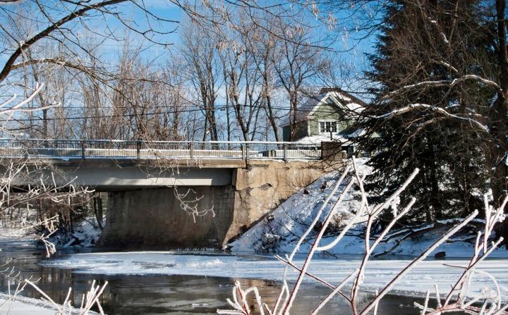 Vue sur une rivière sous un pont enneigé
