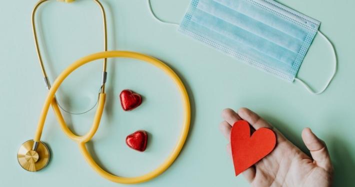 Vu de haut sur un stéthoscope, un masque jetable accompagnés de petits coeurs rouges