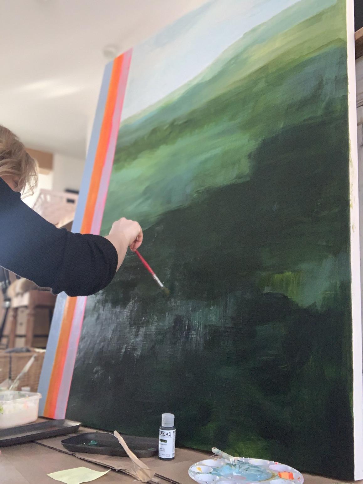 Marie-Claude Lord en processus de création sur une toile recouverte de plusieurs teintes de verts et de bleus