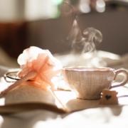 Tasse de thé bouillante déposée sur un calepin avec un crayon