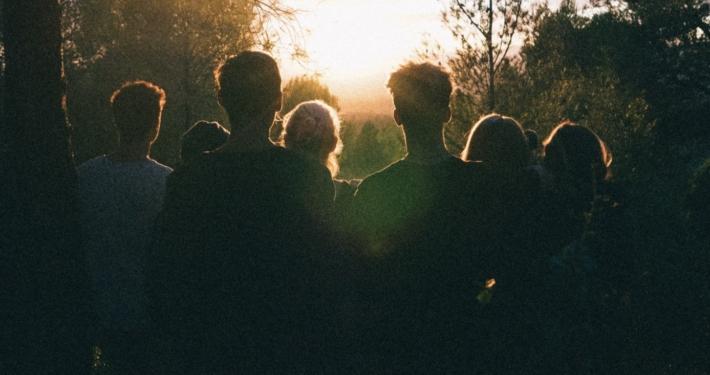 Groupe de personnes de dos regardant le couché de soleil