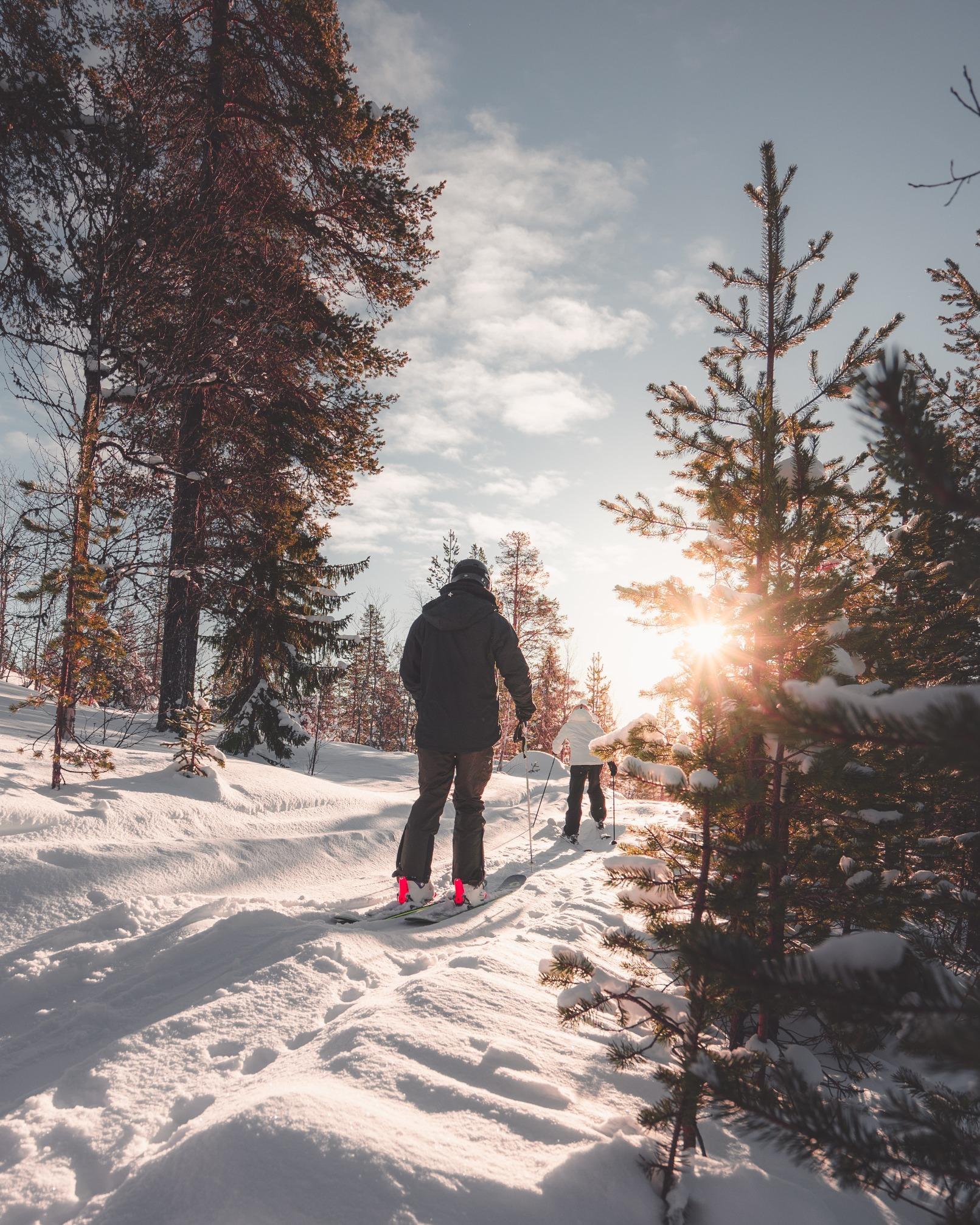 2 personnes faisant du ski de fond sous le couché de soleil